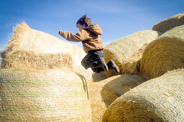 boy playing on hay bales