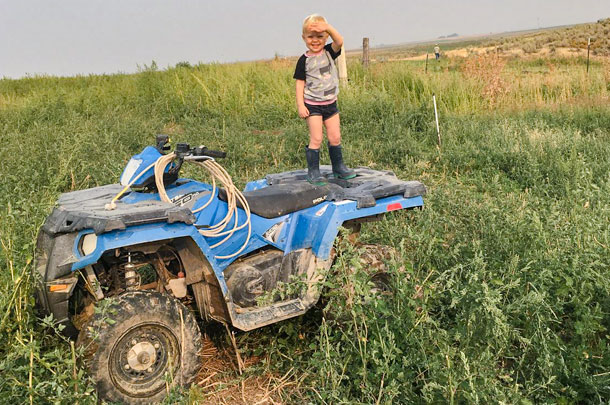 child standing on four-wheeler